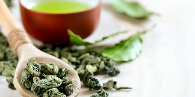 Dried green tea leaves and a fresh hot cup